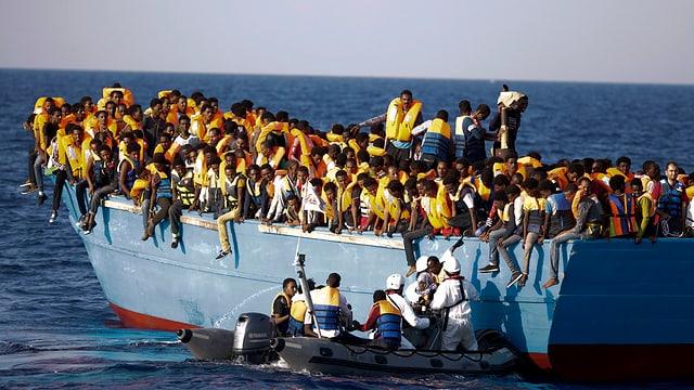 Ein Schlauchboot mit Soldaten vor einem überfüllten Holzboot.