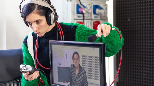 Eine Frau mit Kopfhörer und Mikrofon steht hinter einem Bildschirm.