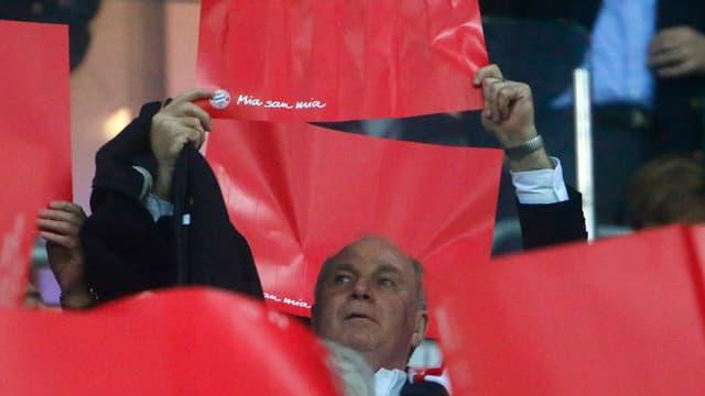 Uli Hoeness hält ein rotes Papier in die Luft.
