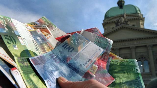 Mann hält Banknoten vor Bundeshaus.