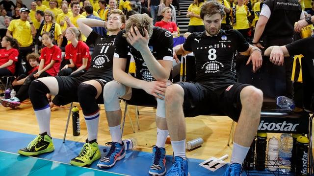 Mehrere Volleyball-Spieler blicken zu Boden, vergraben die Hände in den Haaren oder schauen in die Luft.