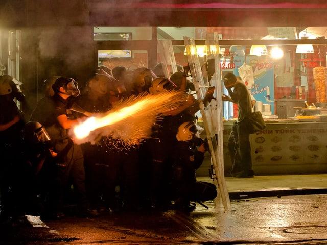 Ein Polizist feuert Tränengas in Richtung Demonstranten