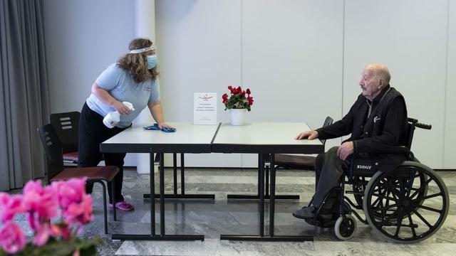 Eine Frau reinigt einen Tisch, ein älterer Mann sitzt im Rollstuhl.