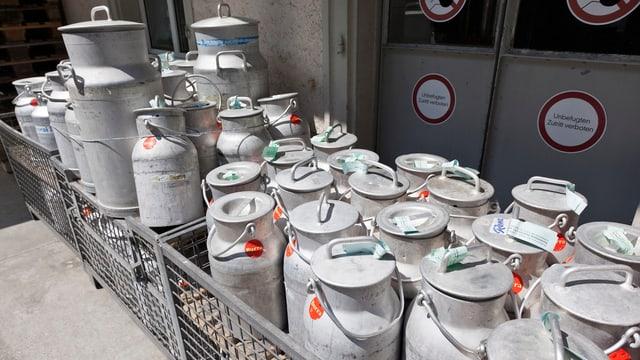 Milchkannen stehen vor einer Milch-Abladestelle