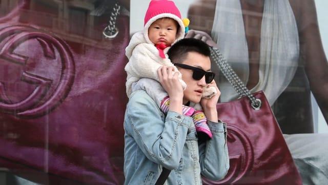 Ein Chinese mit einem Baby auf den Schultern vor einem Gucci-Plakat.
