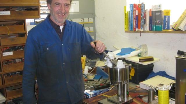 Daniel Pfister steht im blauen Arbeitskleid neben einer selbstgebauten Kaffeemaschine.