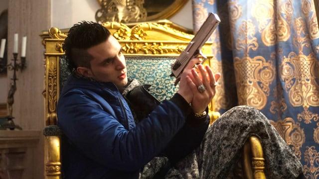 Ein junger Mann sitzt in einem Stuhl mit goldenen Verzierungen. Er hält eine Waffe in der Hand.