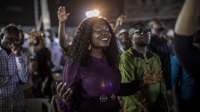 Eine Frau hält die Hände hoch. Sie hat die Augen geschlossen.