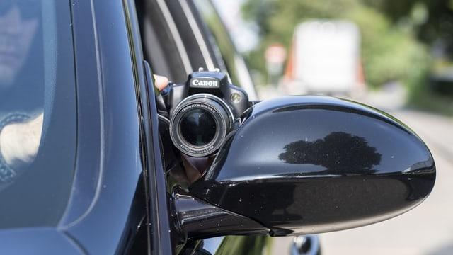 Sozialdetektiv reckt Kamera aus dem Auto