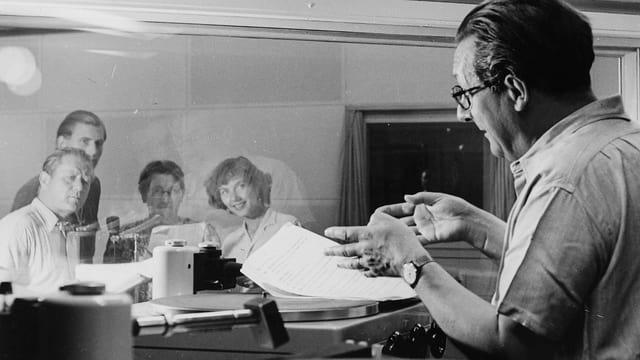 Hörspielaufnahmen von «Polizischt Wäckerli» (1950). Regisseur Artur Welti (rechts) gibt den Schauspieler*innen im Aufnahmeraum Anweisungen: v.l.n.r. Lee Ruckstuhl, Fritz Scheidegger, Schaggi Streuli und Lisa Ruckstuhl.