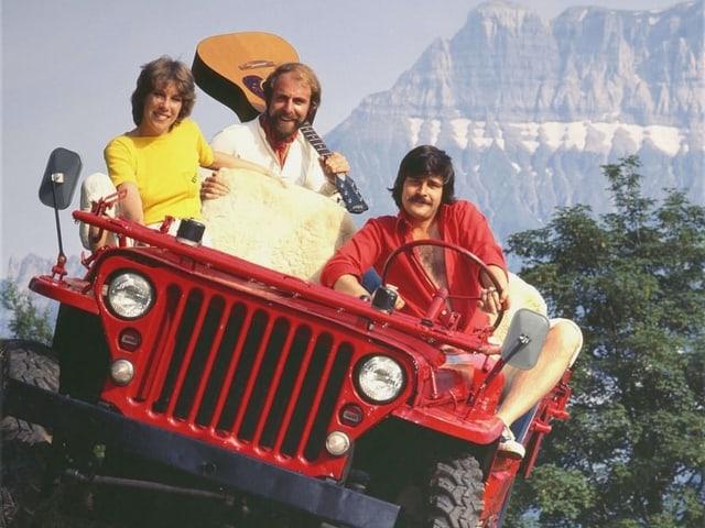 Zwei Männer und Frau auf schief stehendem Traktor. Im Hintergrund Berg.