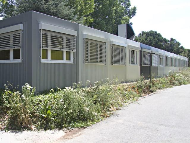 Eine Reihe von grauen, temporären Wohncontainern.