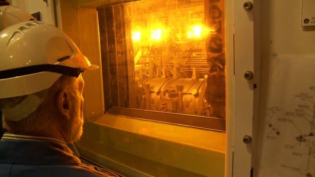 Ein Mann mit Schutzhelm blickt durch ein Fenster auf ein hell beleuchtetes Gerät