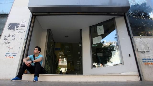 Ein junger Mann sitzt vor der Türe eines Büros auf dem Boden.