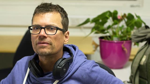 Olivier Kugler im violetten Hoodie mit Kopfhörer um den Hals.