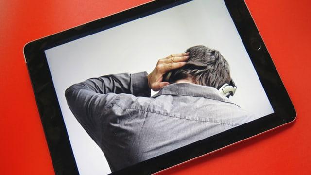 Ein Tablet, das ein Foto zeigt, auf der ein Mann Kopfhörer trägt.
