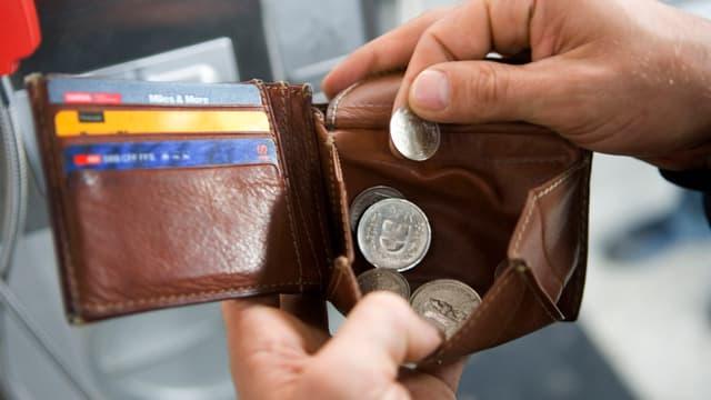 Symbolbild Geld. Person holt Münzen aus einem Portmonee