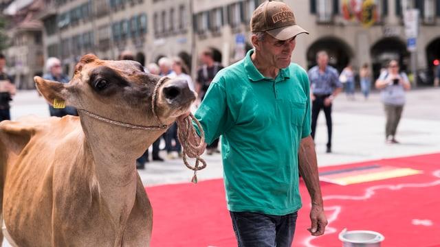 Mann mit Kuh vor städtischer Kulisse.