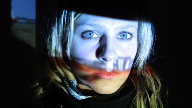 Filmprojektion auf das Gesicht einer Frau.