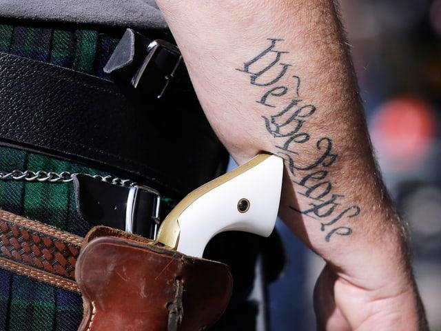 """Nahaufnahme: Ein Mann trägt einen Pistolengurt mit Pistolengriff, auf seinem Arm ist das Tattoo """"We the People"""" zu sehen."""