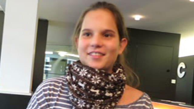 Ein Mädchen in einem gestreiften Pulli mit einem braun-weissen Schal