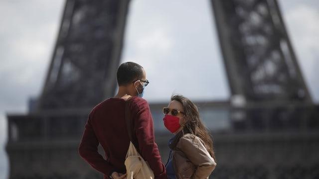 Duas persunas cun mascrina davant la tuor Eiffel.