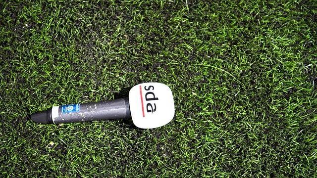 Mikrofon das auf grünem Rasen liegt, SDA-Logo ist sichtbar.