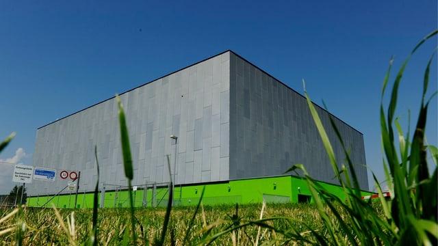 Eine grosse Industriehalle neben einem Kornfeld unter blauem Himmel.