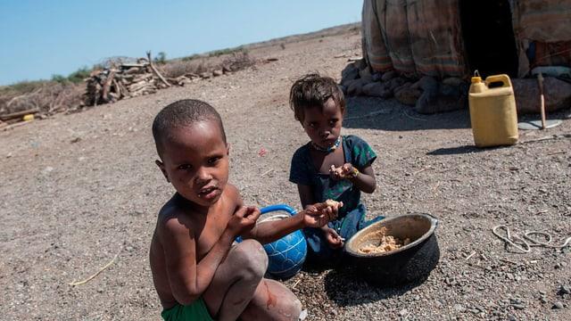 Schwarze Kinder im afrikanichen Niemandsland essen aus einem Topf.