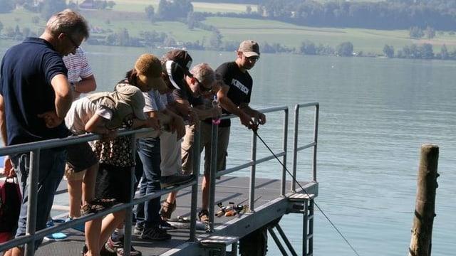 Menschen stehen auf einem Steg und fischen.