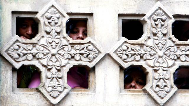 Menschen spähen durch ein mit Kreuzen verziertes Fenster im Marienkloster in Dronka.