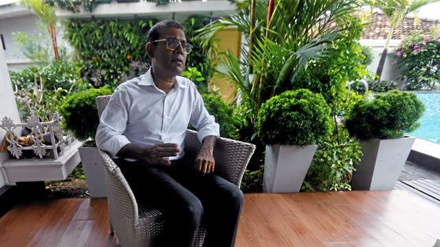 Nasheed sitzt in einem Stuhl und spricht.