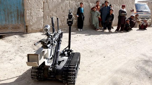 Ein Roboter sucht 2011 in Afghanistan nach Bomben, im Hintergrund betrachtet eine Gruppe Kinder ihn.