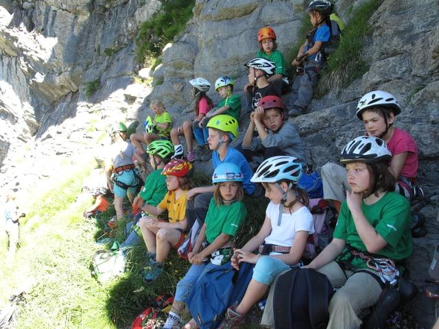 Gruppe von Kindern eines Kletterlagers, die im Schatten sitzen.