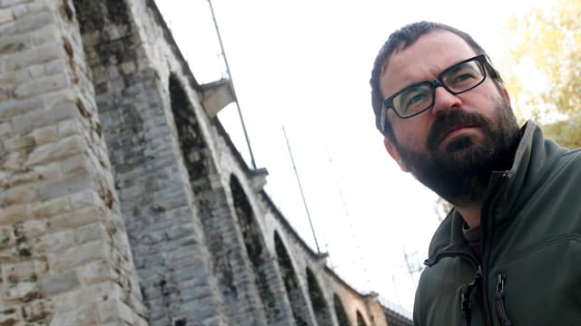 Max Küng, mit Brille und Bart, vor den Bögen des Viaduktes in Zürich stehend, zur Seite blickend.