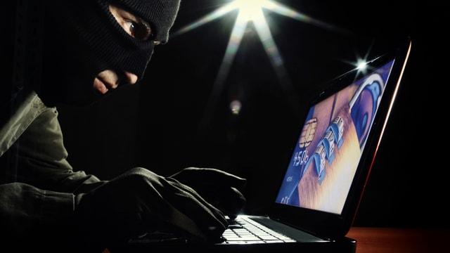 Ein maskierter Mann benutzt seinen Laptop für kriminelle Aktivitäten
