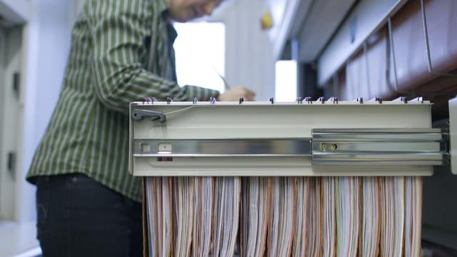 Eine Frau vor einer geöffneten Aktenschrank-Schublade mit Hängeregistern.