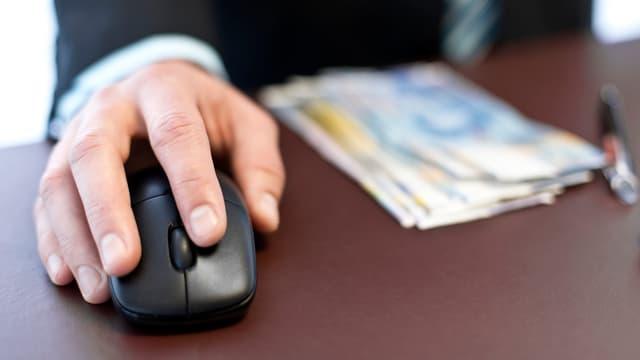 Eine Hand auf einer Computer-Maus, daneben Geldscheine.