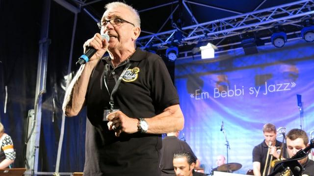 Ernst Mutschler mit Mikrofon auf der Bühne.