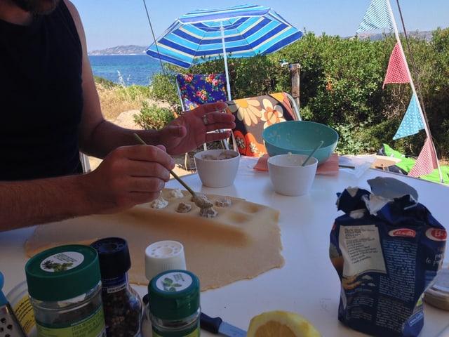 Jemand füllt Ravioli mit Ricotta und Artischocken auf dem Camping