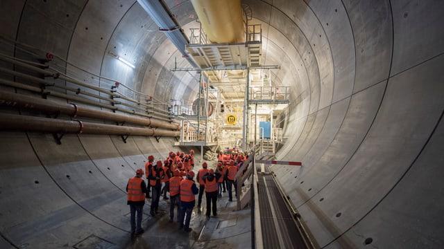 Besucher im Tunnel, im Hintergrund grosse Bohrmaschine