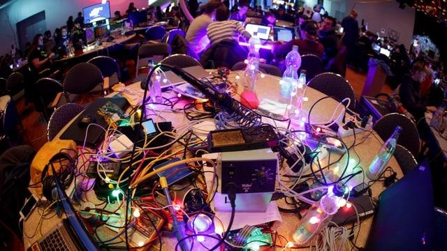 Tisch am CCC-Kongress: Computer und viele Kabel, bunt beleuchtet.