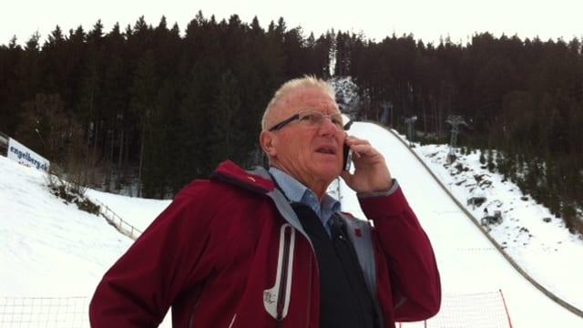 Ok-Präsident Ernst von Holzen am Natel vor der Sprungschanze in Engelberg