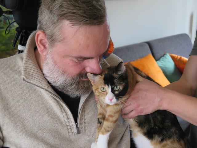 Stefan Csombo hält den Kopf an seine Katze.