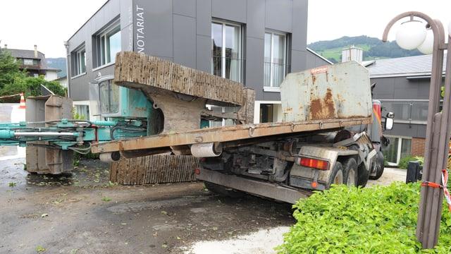 Der Lastwagen und der gekippte Bagger beim Haus.