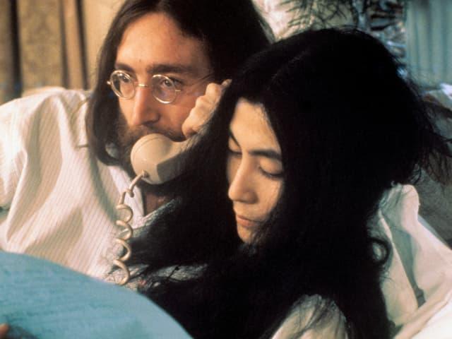 Mann und Frau liegen im Bett.
