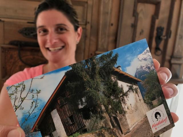 Riccarda Trepp hält eine Postkarte vom Heididorf in die Kamera.