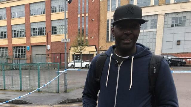 Paul McKenzie mit schwarzer Baseball-Kappe auf einer Strasse.