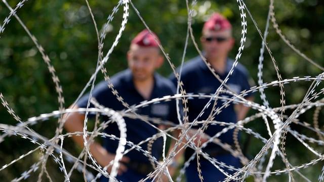 Ungarische Polizisten hinter einem Stacheldrahtzaun