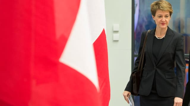 Sommaruga an einer Schweizer-Fahne vorbeigehend.